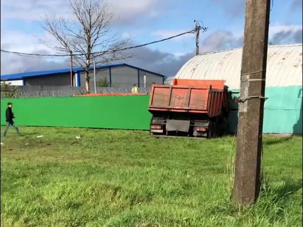 КАМАЗ при съезде с КАД протаранил грузовик и отбойник и воткнулся в стену ангара